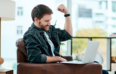 Buy stock photo Shot of a young man using a laptop on the sofa at home and cheering