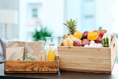 Buy stock photo Shot of a box full of fresh produce on a kitchen counter at home