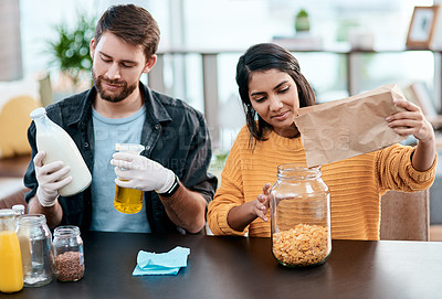 Buy stock photo Shot of a young couple disinfecting their groceries at home