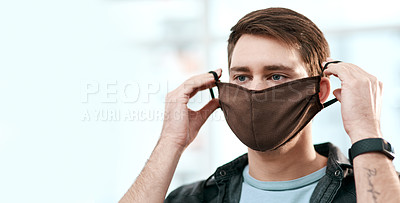 Buy stock photo Shot of a young man putting on a mask at home