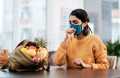 Buy stock photo Shot of a masked young woman coughing after returning home from buying groceries