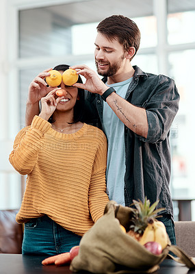 Buy stock photo Shot of a happy young couple having fun while unpacking their healthy groceries at home