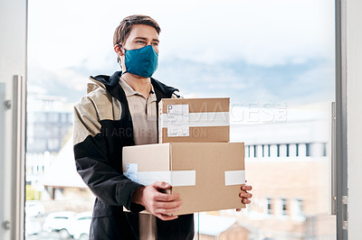 Buy stock photo Shot of a masked young man delivering delivering a package to a place of residence