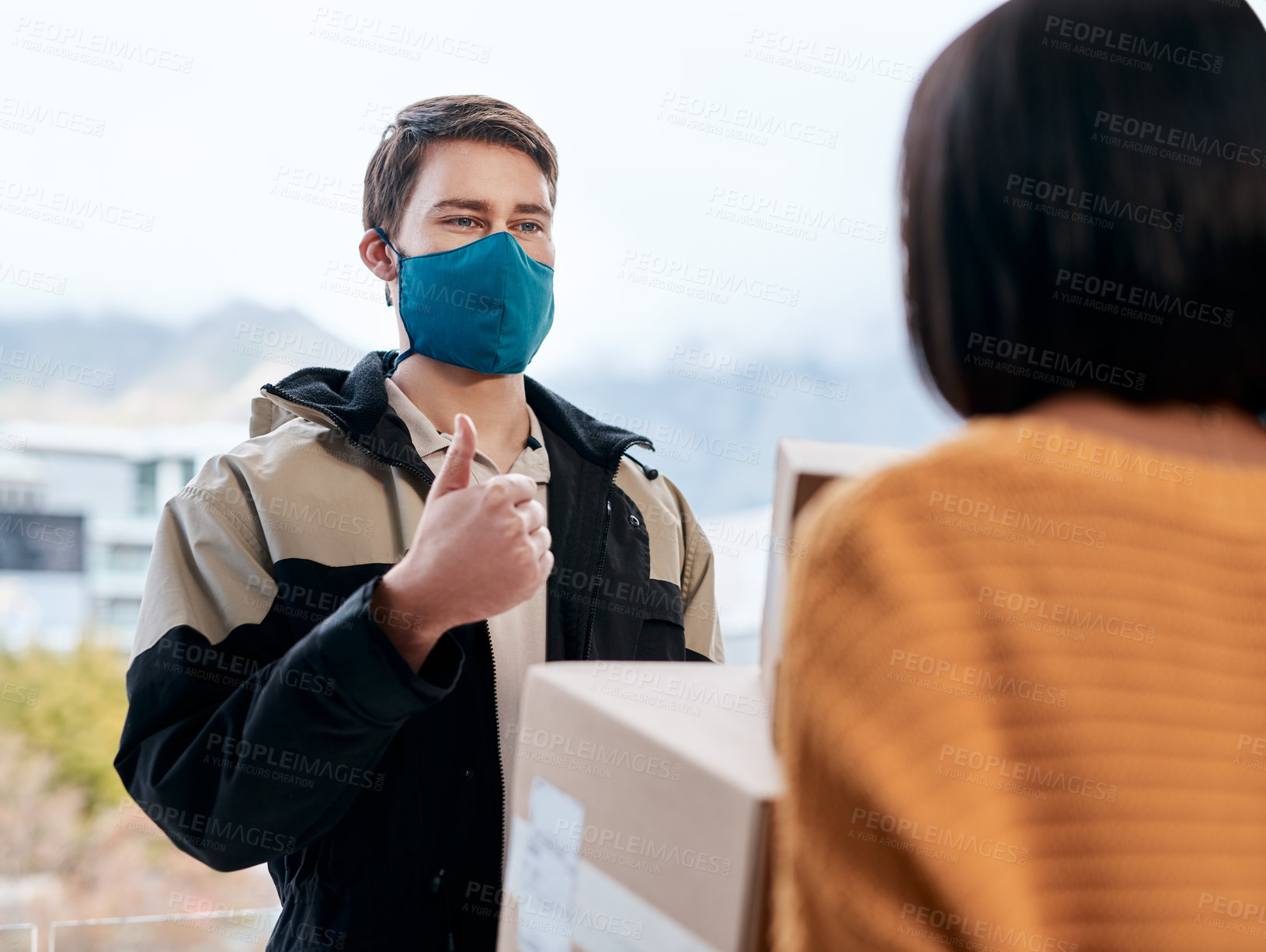 Buy stock photo Shot of a masked young man showing thumbs up while delivery a package to a customer at home