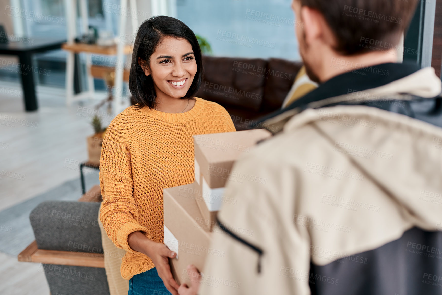 Buy stock photo Shot of a young woman receiving a package from a delivery man at home