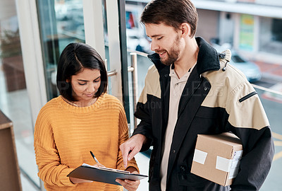 Buy stock photo Shot of a young woman signing for a delivery received at home