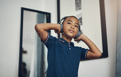 Buy stock photo Cropped shot of a young boy listening to music through headphones at home
