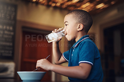 Buy stock photo Shot of a young boy drinking water with his food at home