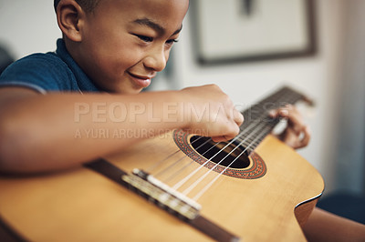 Buy stock photo Shot of a young boy playing the guitar at home