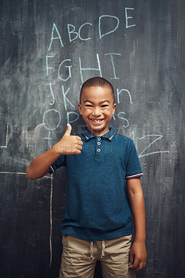 Buy stock photo Shot of a young boy showing thumbs up after writing the alphabet on a blackboard