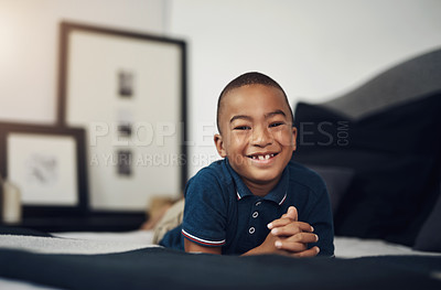 Buy stock photo Shot of an adorable little boy lying on his bed at home