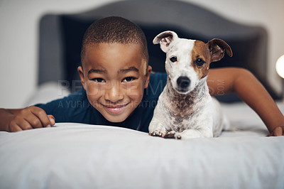 Buy stock photo Shot of an adorable little boy playing with his pet dog on the bed at home