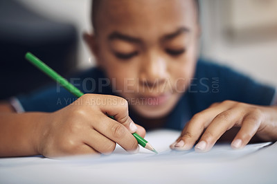 Buy stock photo Shot of a young boy using colouring pencils while drawing at home