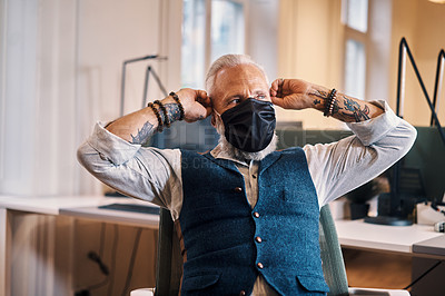 Buy stock photo Cropped shot of a handsome mature businessman looking thoughtful while sitting in his office wearing a mask