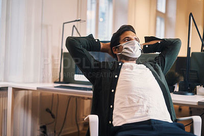 Buy stock photo Cropped shot of a handsome young businessman looking thoughtful while sitting in his office wearing a mask