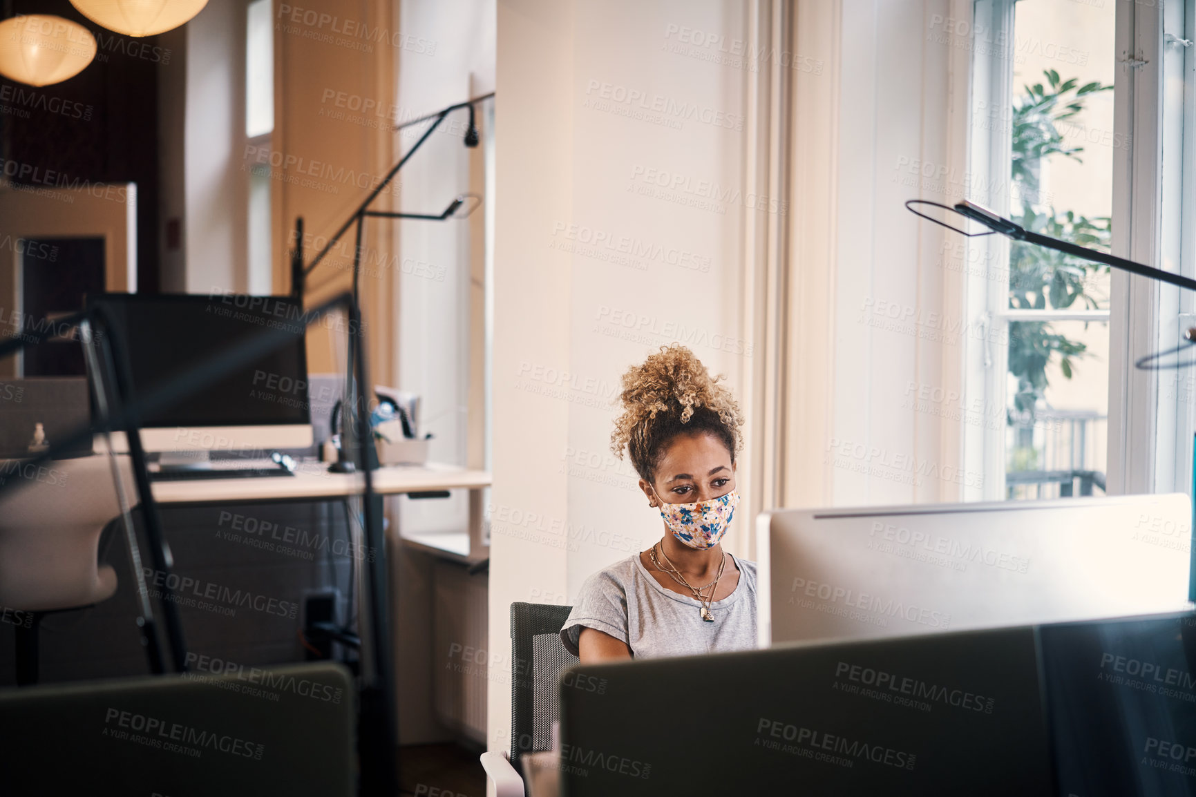Buy stock photo Cropped shot of an attractive young businesswoman wearing a mask while working in the office