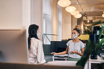 Buy stock photo Cropped shot of two attractive young businesswomen having a discussion in their office while wearing masks