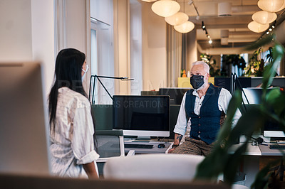 Buy stock photo Cropped shot of two business colleagues having a discussion in their office while wearing masks
