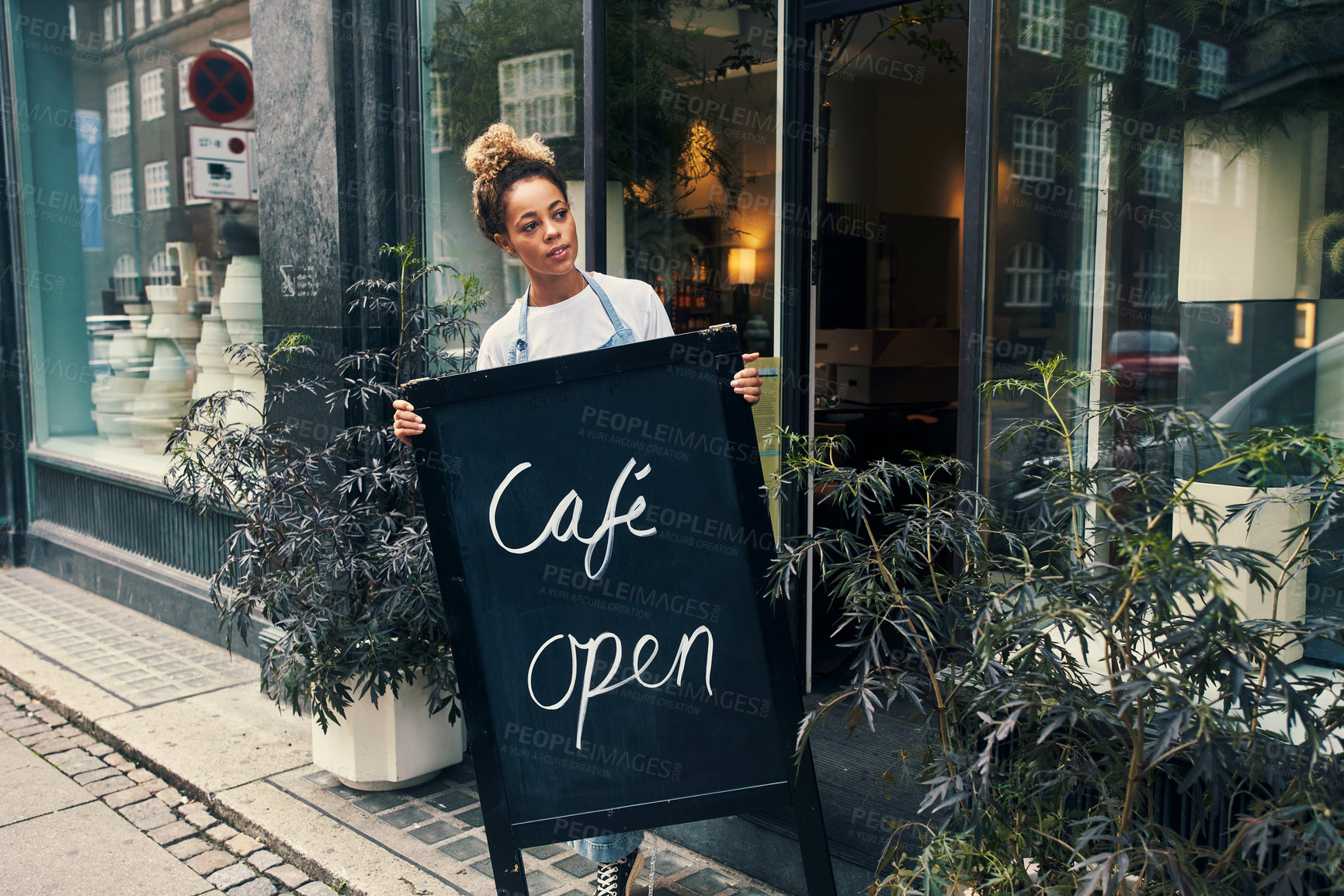 Buy stock photo Shot of a young woman displaying an open sign on the sidewalk of her cafe