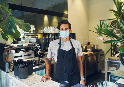 Buy stock photo Shot of a masked young man working in a cafe