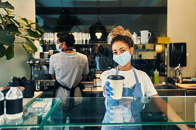 Buy stock photo Shot of a masked young woman serving a freshly brewed cup of coffee in a cafe