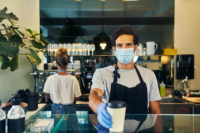 Buy stock photo Shot of a masked young man serving a freshly brewed cup of coffee in a cafe