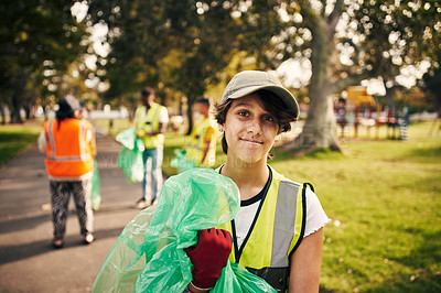 Buy stock photo Cropped portrait of a young female volunteer doing community service in the local park with her friends in the background