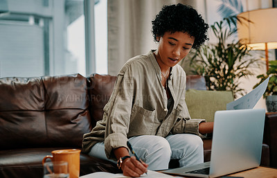 Buy stock photo Shot of a woman making notes while using her laptop at home
