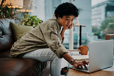 Buy stock photo Cropped shot of a young woman using her laptop while sitting with her notebook at home