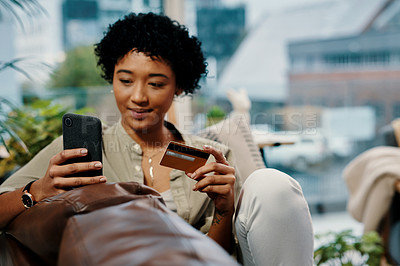 Buy stock photo Shot of a young woman holding her credit card while using her cellphone at home