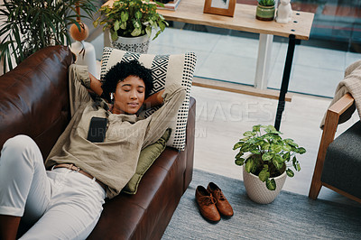 Buy stock photo Shot of a young woman wearing wireless earphones while lying with her cellphone on her chest