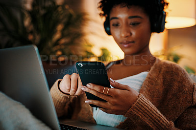 Buy stock photo Shot of a young woman using her cellphone while sitting with her laptop at night