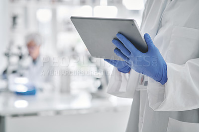 Buy stock photo Closeup shot of an unrecognisable scientist using a digital tablet in a lab