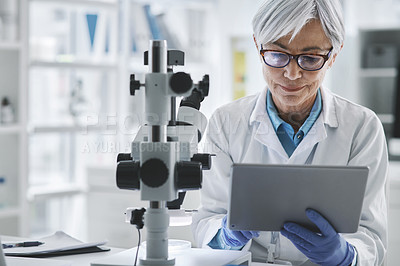 Buy stock photo Shot of a mature scientist using a digital tablet in a lab