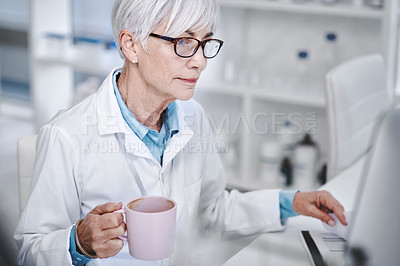 Buy stock photo Shot of a mature scientist drinking coffee while working in a lab