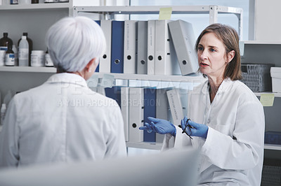 Buy stock photo Shot of a mature scientist having a discussion with a colleague in a lab