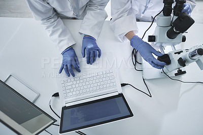 Buy stock photo High angle shot of two unrecognisable scientists working in a lab