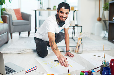Buy stock photo Shot of a young man painting while sitting on the floor at home
