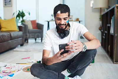 Buy stock photo Shot of artist using his cellphone after painting at home