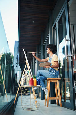 Buy stock photo Shot of a young artist painting on a canvas while sitting on the balcony at home