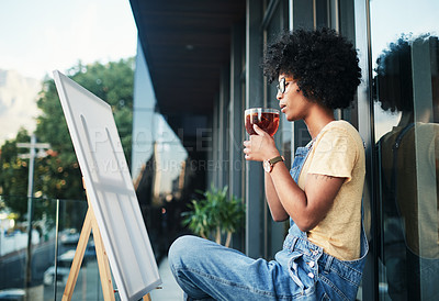 Buy stock photo Shot of a young artist having tea while sitting on the balcony with a canvas
