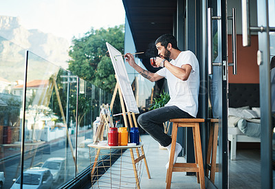 Buy stock photo Shot of a man having tea while doing a painting on the balcony at home