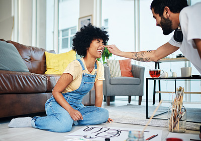 Buy stock photo Shot of a playful couple having fun while painting at home