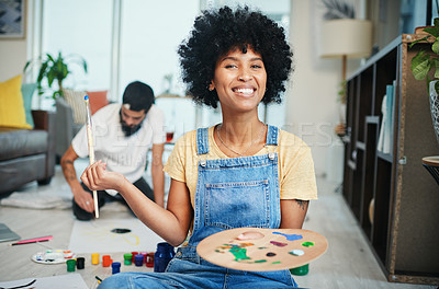 Buy stock photo Shot of a young woman holding a paint palette while her boyfriend sits in the background