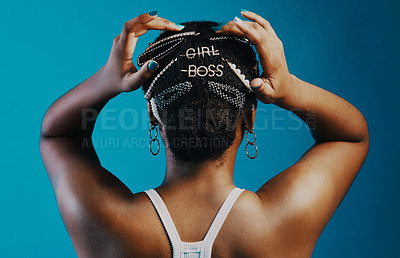 Buy stock photo Rearview shot of a young woman wearing hair clips against a blue background