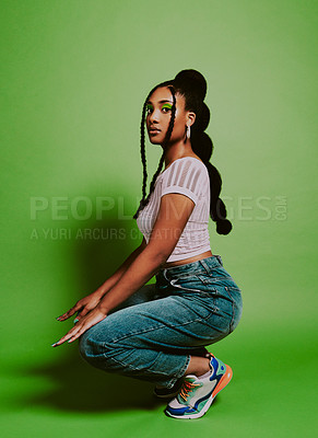 Buy stock photo Shot of a young woman posing against a green background with a trendy hairstyle