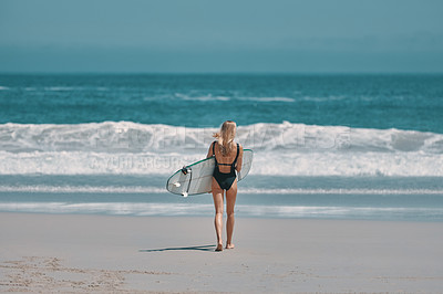Buy stock photo Rearview shot of a young woman carrying a surfboard while walking towards the ocean