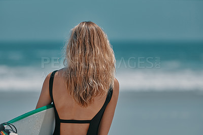 Buy stock photo Rearview shot of a young woman carrying a surfboard at the beach