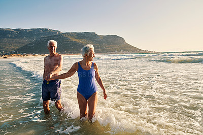 Buy stock photo Shot of a senior couple having fun in the water at the beach