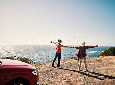 Buy stock photo Rearview shot of a senior couple standing with their arms outstretched during a road trip along the coast